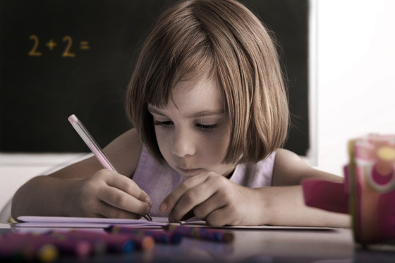 Portrait of a young pupil writing in a classroom